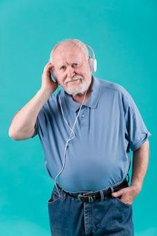Senior de alto ângulo em casa ouvindo música