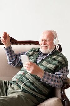 Sênior de alto ângulo sorridente no sofá tocando música