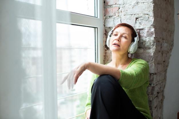 Senior de baixo ângulo, sentado ao lado da janela