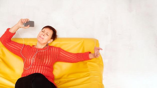 Senior de cópia-espaço no sofá, ouvir música