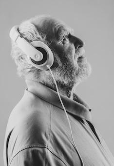 Senior de vista lateral com fones de ouvido