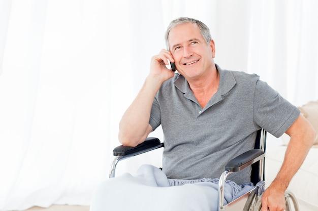 Sénior em sua cadeira de rodas telefonando