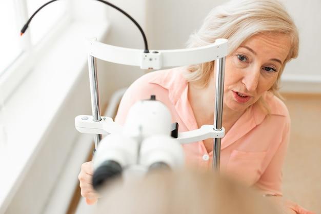 Sênior expressivo de cabelos curtos. mulher loira curiosa com camisa rosa perguntando ao médico sobre o processo de verificação e exame