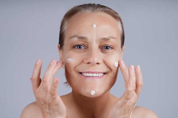 Sênior feliz aplicar creme cosmético no rosto. cuidados com a pele do rosto na velhice.