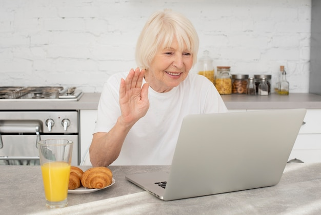 Sênior feliz com um laptop e um copo com suco