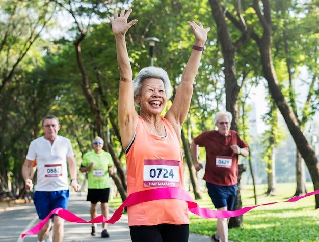 Senior feliz correndo pela linha de chegada