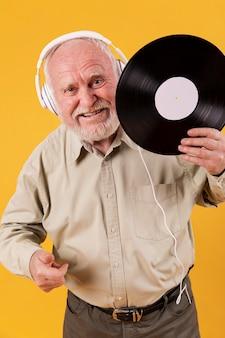 Sênior feliz segurando o registro de música