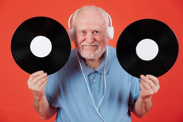 Sênior feliz segurando registros de música