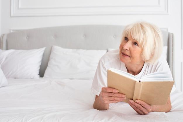 Sênior feliz, segurando um livro