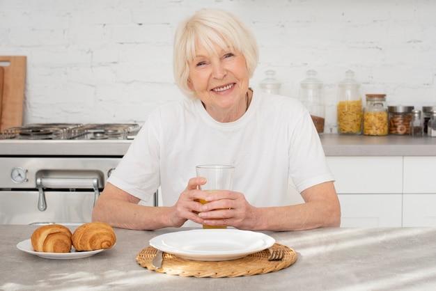Sênior feliz sentado na cozinha