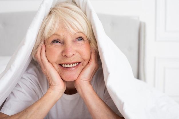 Sênior feliz sentado sob o cobertor