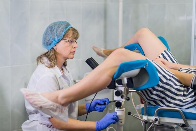 Senior feminino positivamente ginecologista examinando um paciente na clínica, conceito de cuidados de saúde