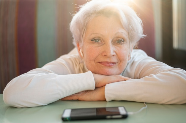 Sênior feminino sentado com a cabeça na mesa e ouvir música