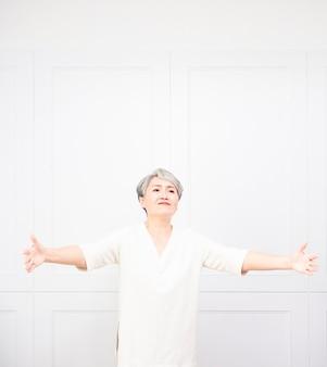 Sênior linda mulher de cabelos grisalhos sorrindo com os braços abertos para um abraço.