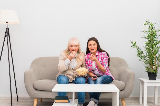 Sênior mãe e filha comendo pipocas enquanto assistia televisão em casa