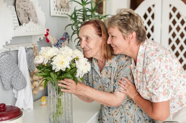Sênior mãe e filha madura cheirando flores de vaso em casa