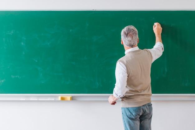 Senior masculino professor escrevendo no quadro negro com giz