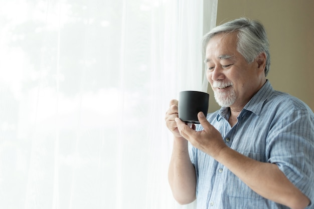 Senior masculino se sentir feliz bebendo café da manhã, aproveitando o tempo em sua casa
