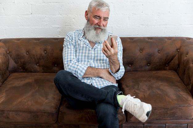 Senior masculino usando smartphone e sentado no sofá