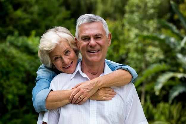 Sênior mulher abraçando o marido por trás contra plantas