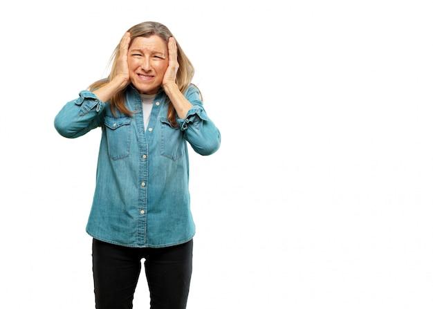 Sênior mulher bonita com ambas as mãos cobrindo as orelhas para protegê-los de um desconfortável, alto, um