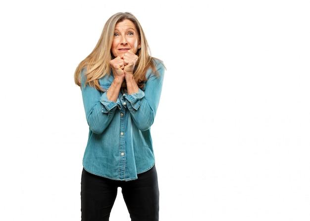 Sênior mulher bonita com um gesto estressado, com ambas as mãos apertadas metade cobrindo o rosto.