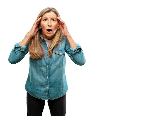 Sênior mulher bonita com uma expressão de surpresa, espantado, segurando as duas mãos na testa e boca