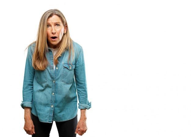 Sênior mulher bonita com uma expressão surpresa e espantada e boca aberta em estado de choque.