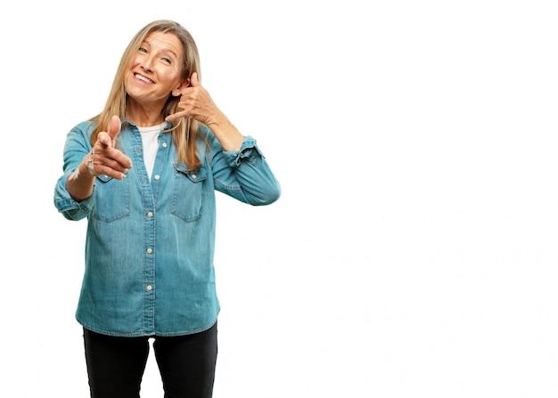 Sênior mulher bonita fazendo um telefonema gesto ou sinal, com um olhar orgulhoso, feliz e satisfeito; fora