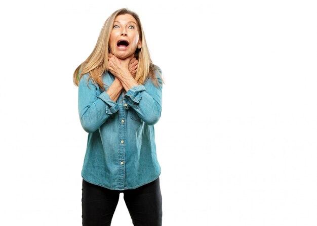 Sênior mulher bonita gritando, olhando surpreso, estressado e aterrorizado, com um gesto de choki