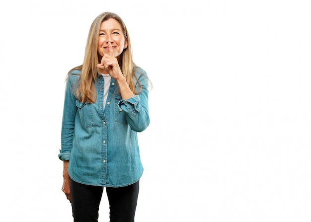 Sênior mulher bonita sorrindo, com o dedo indicador na frente da boca, pedindo silêncio ou partilha de um