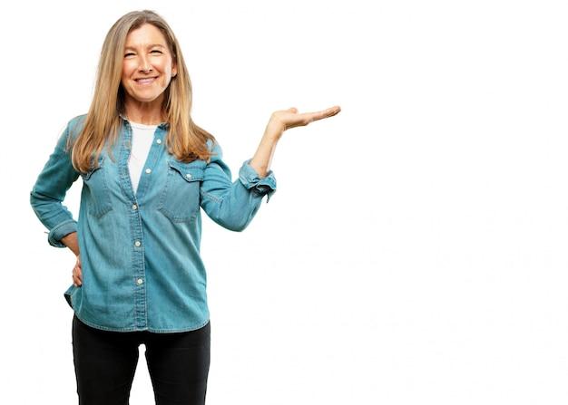 Sênior mulher bonita sorrindo com uma expressão satisfeita mostrando um objeto ou conceito com um han
