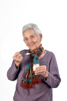 Sênior mulher comer iogurte no fundo branco