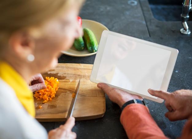 Sênior mulher cozinhando comida cozinha tablet