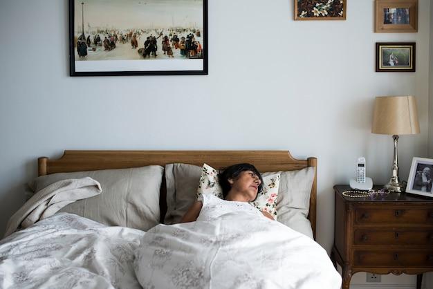 Sênior mulher dormindo sozinha na cama