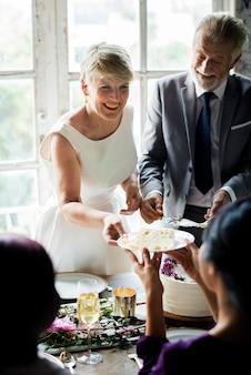 Sênior mulher entregando bolo ao amigo