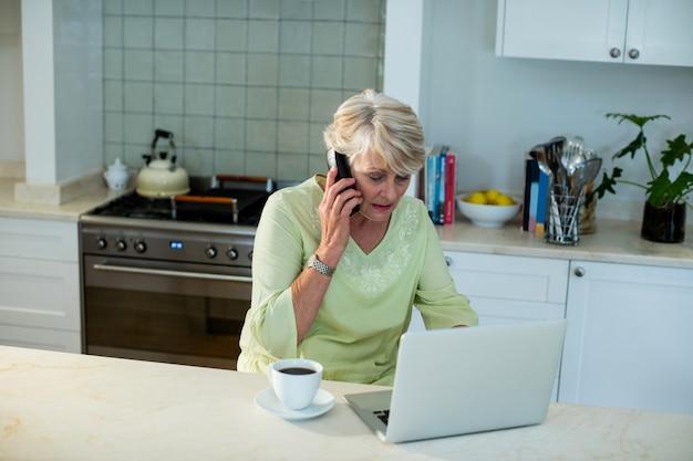 Sênior mulher falando no celular enquanto estiver usando o laptop