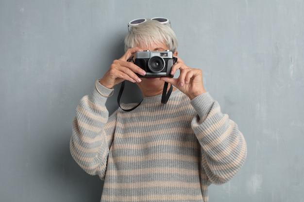 Senior mulher legal com uma câmera de fotografia vintage contra grun