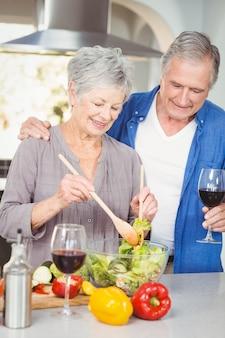 Sênior mulher preparando uma salada enquanto seu marido está de pé no balcão