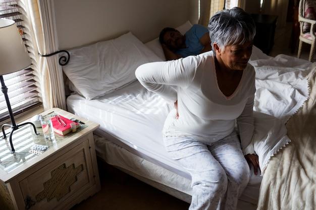 Sênior mulher que sofre de dor nas costas no quarto