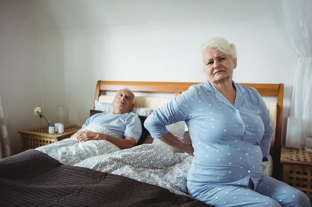 Sênior mulher que sofre de dor nas costas, sentada na cama