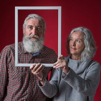 Sênior mulher segurando a borda do quadro branco na frente do rosto do marido contra o pano de fundo vermelho