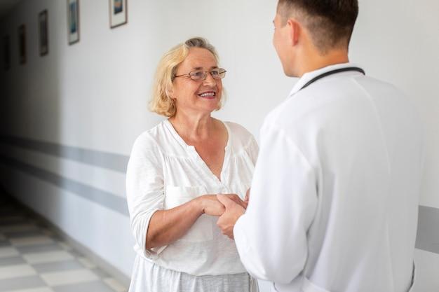 Sênior mulher segurando as mãos do médico