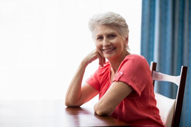 Sênior mulher sentada à mesa