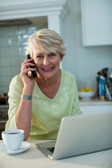 Sênior mulher sentada com laptop e falando no celular