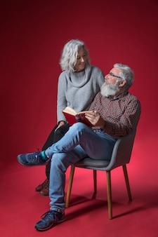 Sênior mulher sentada com o marido sentado na cadeira, segurando o livro na mão contra o fundo vermelho
