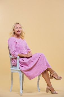 Sênior mulher sentada na cadeira vintage