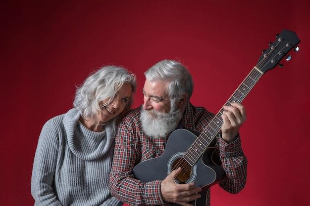 Sênior mulher sentada perto de seu marido tocando violão contra o pano de fundo vermelho