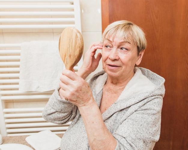 Sênior mulher tocando a pele do rosto macio e olhando no espelho de mão em casa