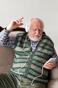 Sênior no sofá tocando música